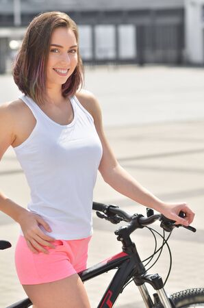 Portrait of beautiful young woman cycling in the city. Summer day
