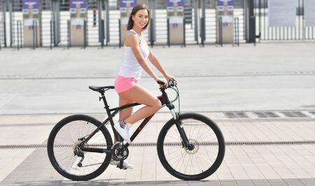 Smiling happy girl in white t-shirt and pink shorts and riding bicycle on a city street and looking at camera
