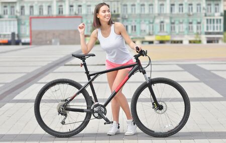 Full body portrait of a beautiful stylish woman dressed in white t-shirt standing with bicycle outdoors Reklamní fotografie