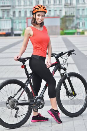 Sexy fitness.Young seductive woman in black sport wear posing outdoor on the bicycle