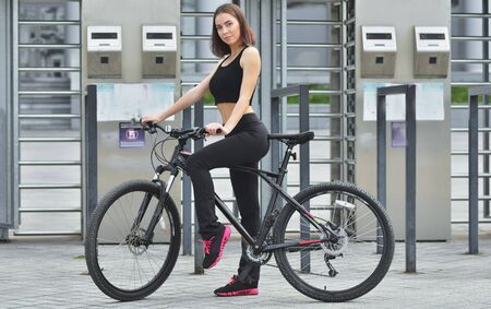 Young beautiful girl standing with her bicycle Reklamní fotografie