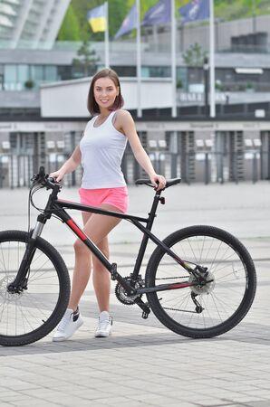 Pretty fit girl is riding on bike in the city Reklamní fotografie