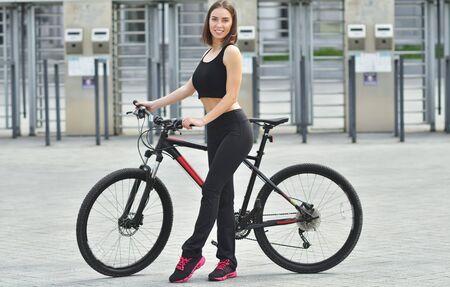 Pretty fitness girl with sport bike is walking in the city Reklamní fotografie