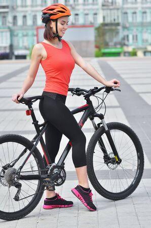 Portrait of sexy fitness girl in helmet with sport bike is walking in the city