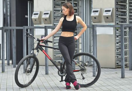 Young fitness girl with sport bike is walking in the city