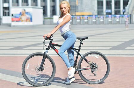 Pretty fitness girl dressed in outfit with sport bike is walking in the city Reklamní fotografie