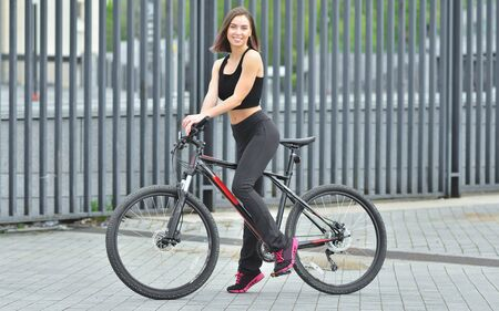 Young beautiful girl standing with her bicycle outdoor Stock fotó
