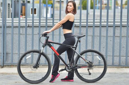 Sports girl with a bicycle in the city. Warm summer day.
