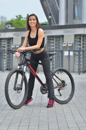 Sport. Beauty fit girl is riding a bike on an open road to the sunset.