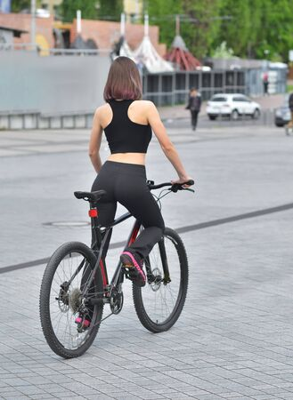 Sexy fitness.Young seductive woman in black sport wear posing outdoor on the bicycle at the stadium