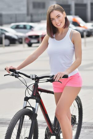 Portrait young beautiful smiling girl wearing a white t-shirt and pink short rides a bicycle through the streets of the city