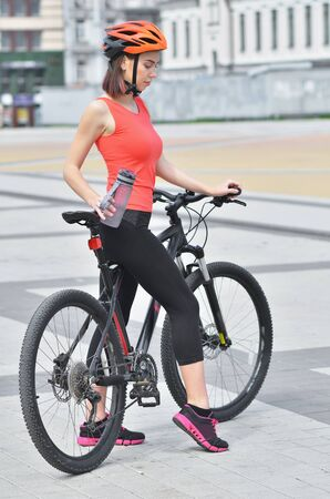Fit girl is riding bikes through the streets of the city and smiling Stock fotó