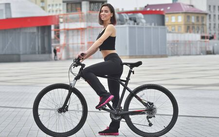 Portrait of a pretty young woman rides a bicycle through the streets of the city. Summer day