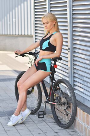 Young seductive blonde woman in black sport wear posing outdoor on the bicycle at the stadium