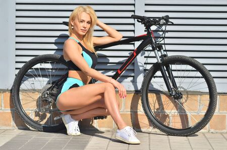 Pretty sport girl in a tracksuit, with bicycle is sitting to squat. Urban background