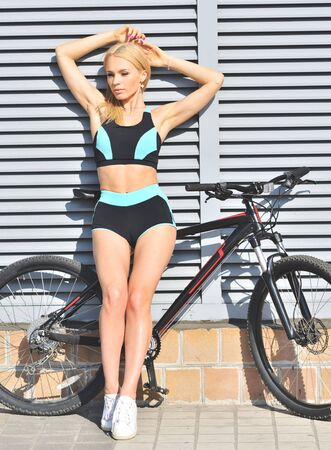 Young prettysport woman in tracksuit standing near gray wall with bicycle. Sport concept