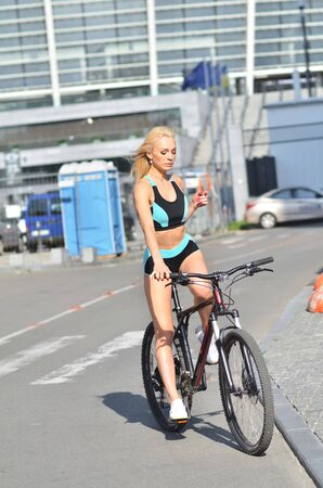 Good girl with sports body rides bicycle, urban background. Attractive blonde sits on bicycle.