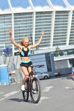 Sport woman in tracksuit rides bicycle on outdoor, urban background. Attractive blonde sits on bicycle.