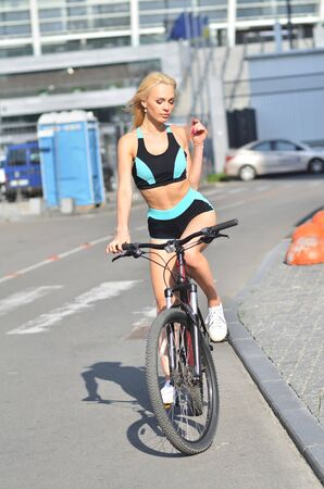 A stunning european sport girl in a tracksuit, with bicycle is sitting to squat. Urban background 免版税图像