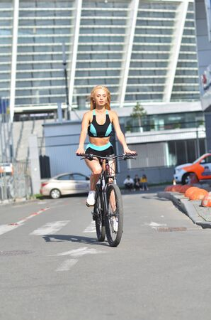 Blonde beautiful girl in tracksuit rides bicycle on outdoor, urban background. Attractive blonde sits on bicycle.