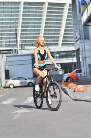 Young beautiful girl in tracksuit rides bicycle on outdoor, urban background. Attractive blonde sits on bicycle. 免版税图像