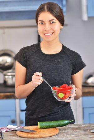 Portrait of cute young asian girl smiling while cooking salad with fresh vegetables in kitchen interior at home.