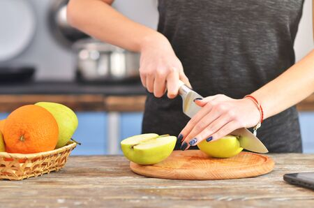 A young woman in a black t-shirt cuts green apple on a light wooden board in a kitchen. Fruit in bowl is standing near. Horizontal photo 免版税图像