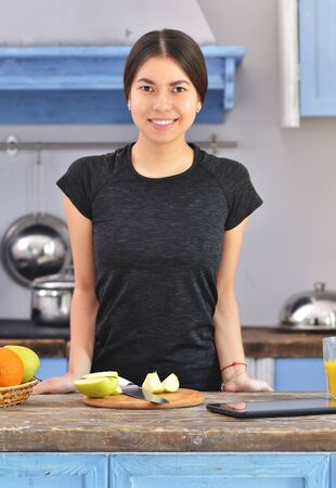 Portrait of a young asian fitness girl in the kitchen. Fruit and tablet on background