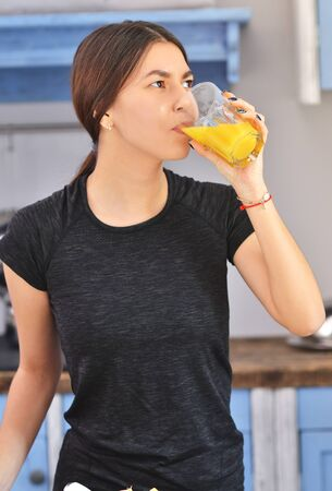 Portrait of a young asian woman in a black t-shirt prepares Breakfast and drinks fresh orange juice in the kitchen. Horizontal photo