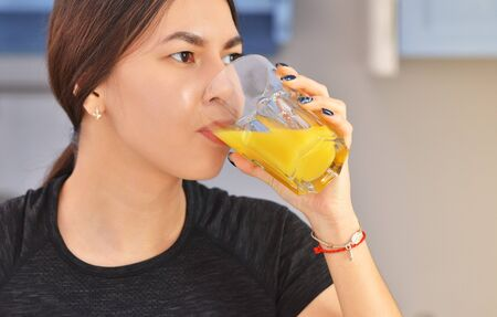 Portrait of a young asian woman in a black t-shirt prepares Breakfast and drinks fresh orange juice in the kitchen . Clouse-up photo