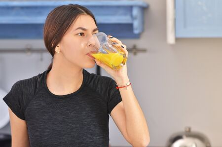 A young asian woman in a black t-shirt prepares Breakfast and drinks fresh orange juice in the kitchen . Horizontal photo