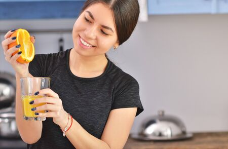 Sport Asian woman in a black t-shirt squeezes orange juice in the kitchen. Horizontal photo