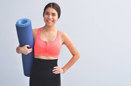 Sporty girl holding yoga mat doing asana over bright gray background