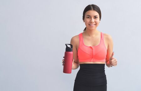 Young athletic woman in fitness equipment having a bottle of water in hand, on gray background