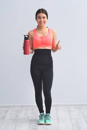 Young happy fitness girl with sporty body drink water at studio on a white background. Beautiful fit Girl. Fitness model in pink sportswear.
