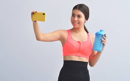 Fitness Apps. Slim Girl Using Smartphone During Workout On Gray Studio Background. Copy Spac