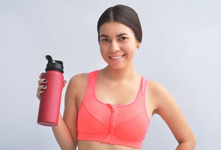 Attractive happy young fit sportswoman standing isolated over gray background, holding a water bottle