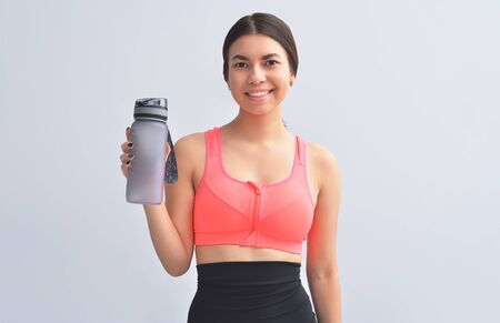 Restoring water balance. Attractive and young woman in sports wear keeping bottle in hand and smiling while standing on gray background