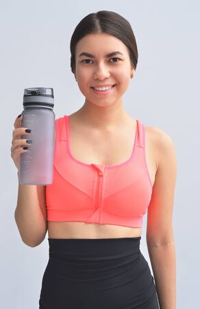 Restoring water balance. Portrait of young woman in sports wear keeping bottle in hand and smiling while standing on gray background