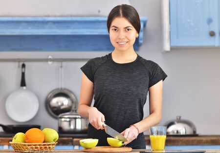 A young girl in a black t-shirt makes a fruit breakfast and cuts apple on a light wooden board in a kitchen. Orange juice and fruit in bowl is standing near. Horizontal photo 免版税图像