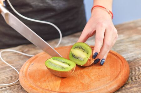 Young woman in sportswear cutting kiwi on chopping board in the kitchen. Clouse-up
