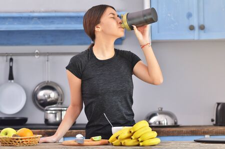 Young asian woman drinking protein shake near table with ingredients in kitchen 免版税图像
