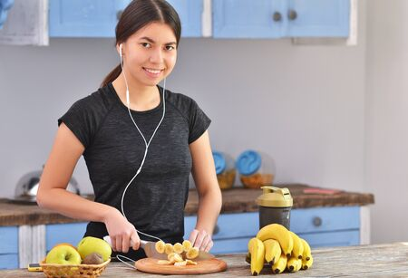 Sporty young woman is preparing healthy food on light kitchen. Green healthy food concept. 免版税图像