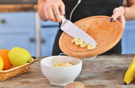 Closeup on woman making fruits salad with bananas