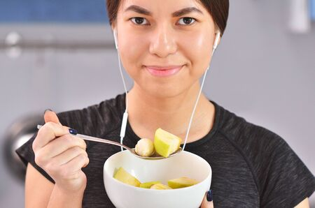 Portrait of young asian girl in the comfort of home kitchen eats fruit salad with banana and listen to music
