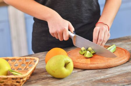 Cropped view of girl cutting tasty kiwi on chopping board. Clouse-up Reklamní fotografie