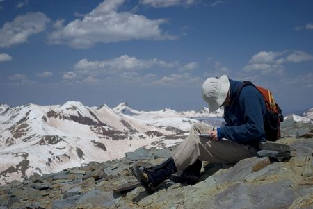 a hiker writing in a journal at the summit of a mountain