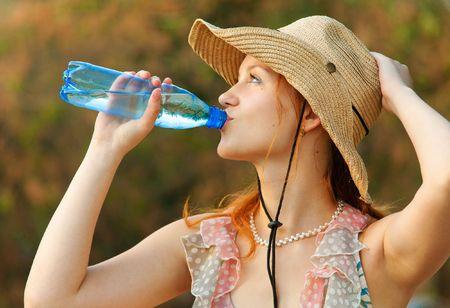 Beautiful girl in straw hat drinks water from bottle photo