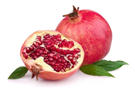Juicy pomegranate and its half with leaves. Isolated on a white background photo