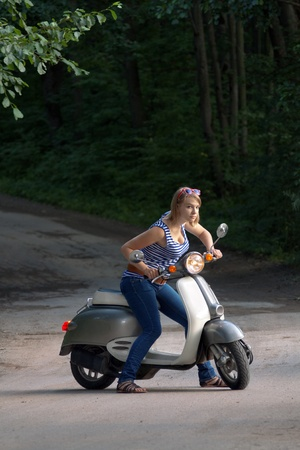 Portrait of young woman on scooter. Outdoor on street photo